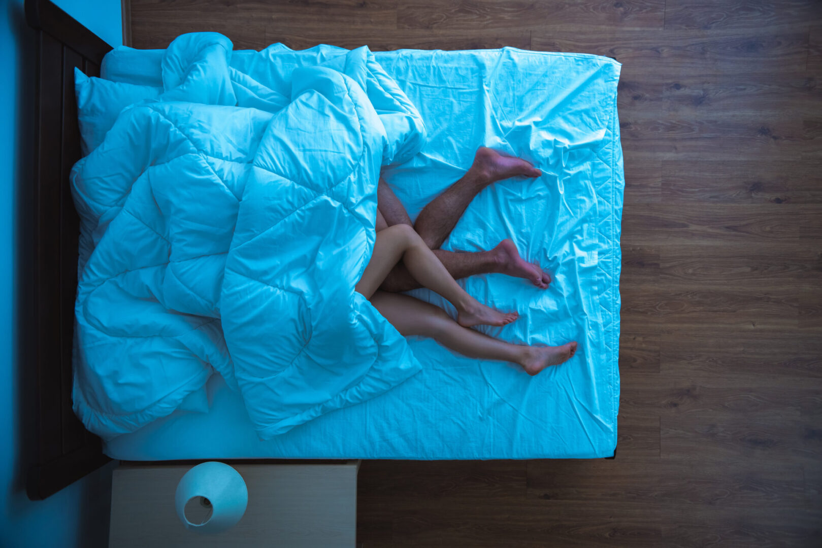 The man and a woman laying under a duvet. evening night time. view from above
